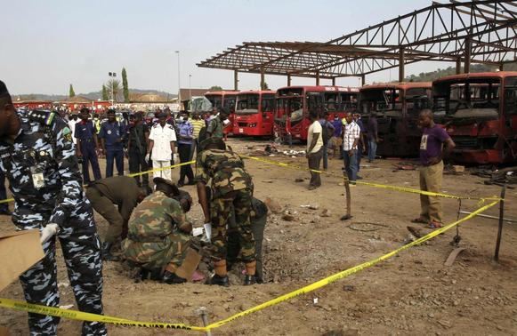 Bomb experts gather evidence in a crater that was caused by a bomb blast explosion at Nyanyan, Abuja April 14, 2014. REUTERS-Afolabi Sotunde