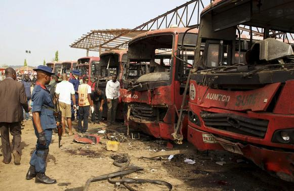 Bomb experts search for evidences in front of buses at a bomb blast scene at Nyanyan in Abuja April 14, 2014. REUTERS-Afolabi Sotunde