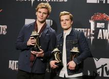"""Los actores Sam Claflin (izquierda) y Josh Hutcherson posan con sus premios por Mejora Película del Año y el premio de Hutcherson por mejor interpretación masculina por """"The Hunger Games: Catching Fire"""" en los MTV Movie Awards, Los Angeles, California, abr 13, 2014. Favorita de los adultos jóvenes, """"The Hunger Games: Catching Fire"""" fue elegida el domingo como la película del año y llevó importantes premios de actuación en los MTV Movie Awards. REUTERS/Danny Moloshok"""