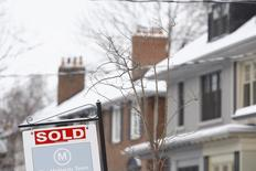 """A """"Sold"""" sign hangs in front of a house in Toronto, Ontario March 2, 2014. REUTERS/Hyungwon Kang"""