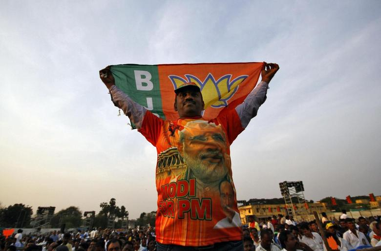 A supporter of Hindu nationalist Narendra Modi, prime ministerial candidate for India's main opposition Bharatiya Janata Party (BJP), holds a party flag during an election campaign rally addressed by Modi in the southern Indian city of Chennai April 13, 2014. REUTERS/Babu