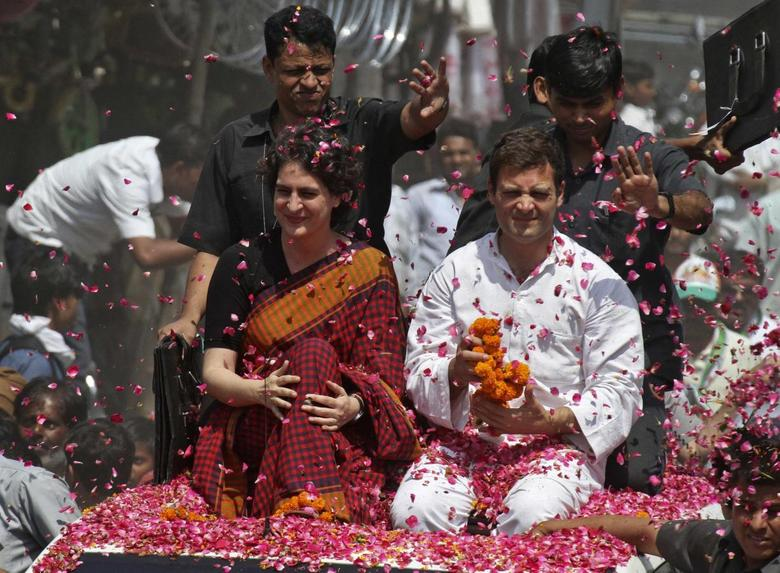 Rahul Gandhi (in white), India's ruling Congress party vice president and son of Congress chief Sonia Gandhi, and his sister Priyanka Gandhi Vadra are showered with rose petals by their supporters upon Rahul's arrival to file his nomination for the general election at Amethi, in the northern Indian state of Uttar Pradesh April 12, 2014. REUTERS/Pawan Kumar