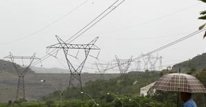 Um morador anda e olha para uma rede de torres de transmissão de energia, em Minas Gerais. Problemas na caldeira da termelétrica Candiota III, usina da Eletrobras e uma das mais modernas instalações a carvão do país, têm prejudicado a continuidade da geração de energia da usina. Os problemas têm levantado dúvidas sobre confiabilidade do empreendimento em momento em que o Brasil precisa de térmicas para compensar o baixo nível dos reservatórios das hidrelétricas. 14/01/2013 REUTERS/Paulo Whitaker