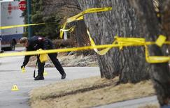 A police officer puts down evidence markers at a house where five people were stabbed in the early morning hours in Calgary, Alberta, April 15, 2014. REUTERS/Todd Korol