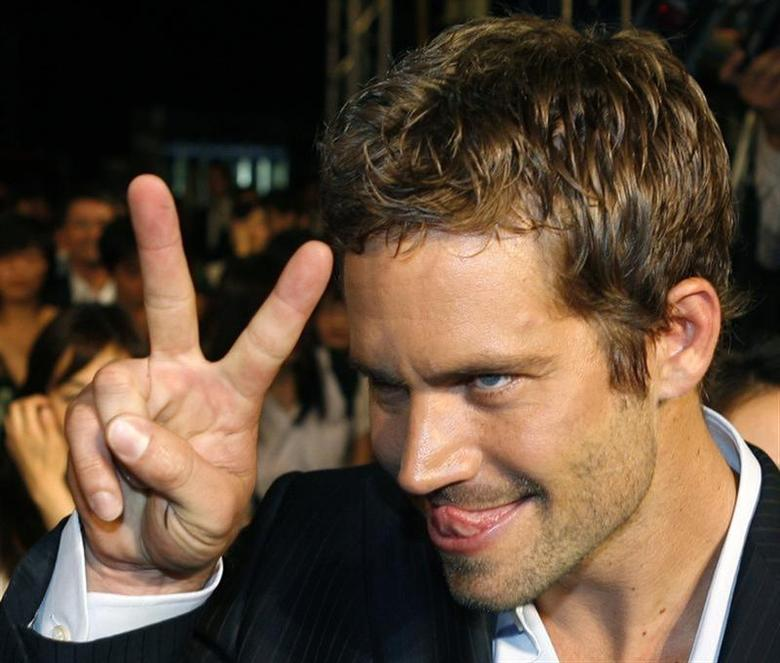 U.S. actor Paul Walker gestures to a fan during the premiere of the movie ''Fast and Furious 4'' in Taipei April 15, 2009. REUTERS/Nicky Loh