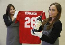 "Employees pose with a bottle of ""Petrus 1988"" wine and a Manchester United Retro Champions League shirt from 1999 signed by retired boss Alex Ferguson, at Christie's auction house in London April 14, 2014. REUTERS/Luke MacGregor"