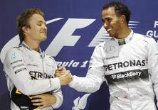 Mercedes Formula One driver Lewis Hamilton of Britain (R) is congratulated by teammate Mercedes Formula One driver Nico Rosberg of Germany on the podium after he won the Bahrain F1 Grand Prix at the Bahrain International Circuit (BIC) in Sakhir, south of Manama April 6, 2014. REUTERS/Thaier Al-Sudani
