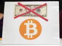 """El logo de Bitcoin debajo de un billete de 5 dólares en una conferencia en Nueva York, abr 8 2014. BTC China, una de las principales casas de cambio de divisa digital del país, instaló el primer cajero automático de bitcoin en el país y lanzó una aplicación online que permite la compra y venta de la moneda a través del teléfono móvil, sorteando una regulación bancaria que es cada vez más hostil para las denominadas """"criptodivisas"""". REUTERS/Lucas Jackson"""
