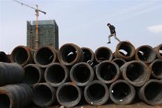 Un cliente salta sobre pilas de cables de acero apilados en un mercado en Jiaxing, China, feb 21 2014. La producción diaria de acero de China alcanzó un récord de 2,27 millones de toneladas en marzo, mostraron datos del Gobierno, mientras las siderúrgicas intensificaban su actividad por expectativas de aumentos estacionales en la demanda. REUTERS/William Hong