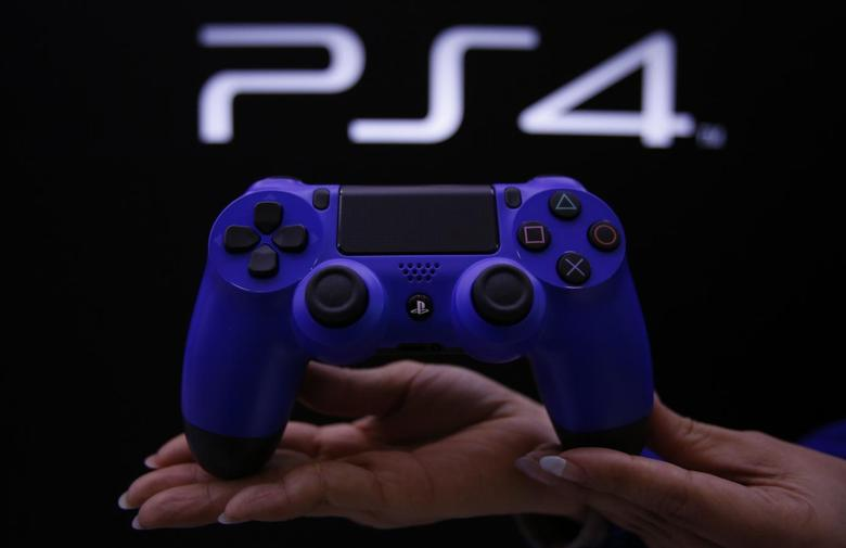 A staff at the PlayStation 4 launch event poses with the PlayStation 4's game controller before its domestic launch event at the Sony Showroom in Tokyo February 21, 2014. REUTERS/Yuya Shino