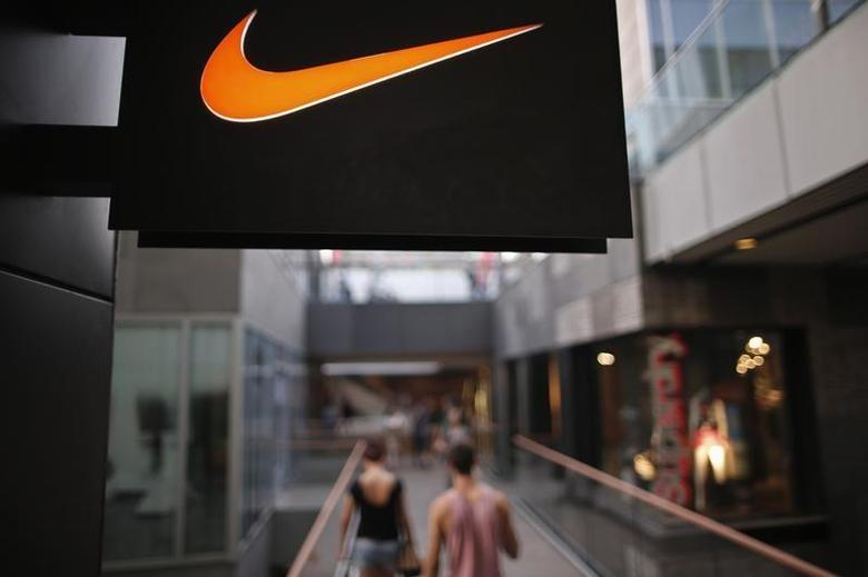 People walks past a Nike shop under the company logo at the Sanlitun shopping area in central Beijing, August 8, 2013. REUTERS/Petar Kujundzic