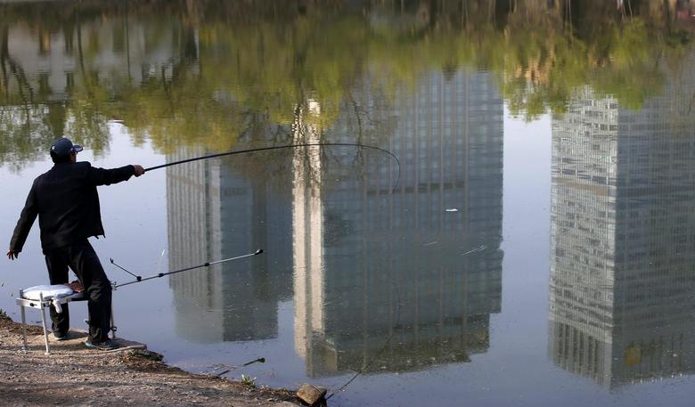A man fishes next to a lake with the reflection of newly-built residential buildings at a park in Shenyang, Liaoning province, April 16, 2014. REUTERS/Stringer