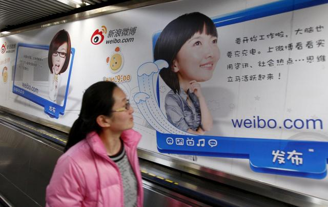 A woman looks at a Weibo advertisement as she rides an elevator inside a subway station in Beijing February 25, 2012. REUTERS/China Daily