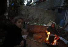 A Palestinian woman burns firewood to cook at her house in the northern Gaza Strip March 20, 2014. REUTERS/Mohammed Salem