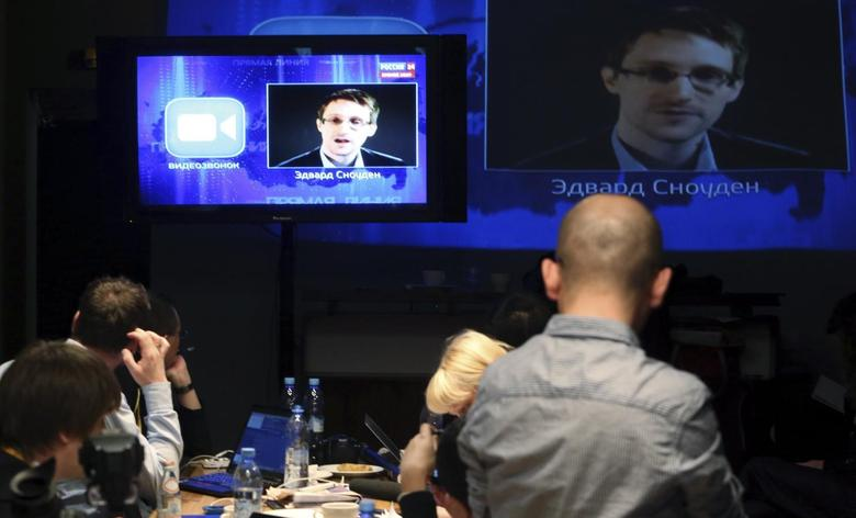 Journalists listen to a speech and a question posed by former U.S. spy agency NSA contractor Edward Snowden, at a media centre during Russian President Vladimir Putin's live broadcast nationwide phone-in, in Moscow April 17, 2014. REUTERS/Sergei Karpukhin