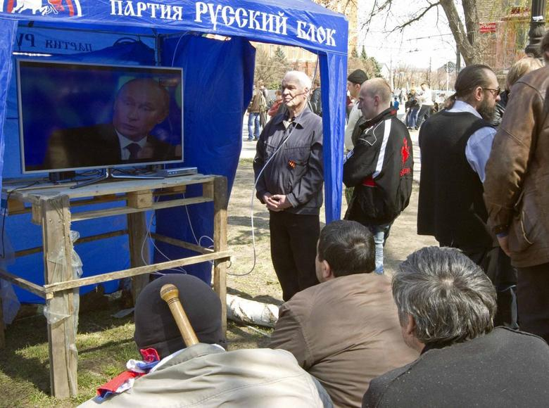 Pro-Russian supporters watch a television broadcast of Russian President Vladimir Putin in Moscow, in their camp near the seized office of the SBU state security service in Luhansk, eastern Ukraine April 17, 2014. REUTERS/Vasily Fedosenko