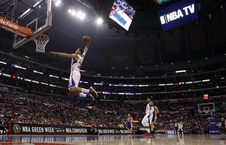 Los Angeles Clippers forward Blake Griffin (L) leaps for a dunk against the Los Angeles Lakers during the first half of their NBA basketball game in Los Angeles, California April 7, 2013. REUTERS/Alex Gallardo