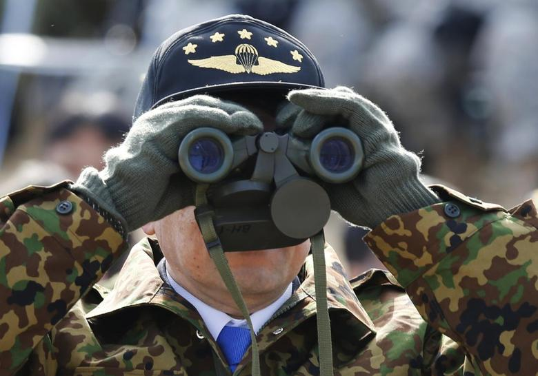 Japan's Defence Minister Itsunori Onodera uses a pair of binoculars as he inspects an annual new year military exercise by the Japanese Ground Self-Defense Force 1st Airborne Brigade at Narashino exercise field in Funabashi, east of Tokyo January 12, 2014. REUTERS/Issei Kato