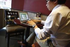 Un hombre trabaja en su notebook en un café en el centro de Shanghái, sep 25, 2013. China limitará la cantidad de dinero que los consumidores pueden trasferir a las plataformas de pago online, en un intento por proteger a bancos y consumidores del fraude en plena explosión de las transacciones online y a través de móviles. REUTERS/Carlos Barría