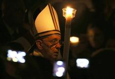 Pope Francis holds a candle as he leads a vigil mass during Easter celebrations at St. Peter's Basilica in the Vatican April 19, 2014. REUTERS/Alessandro Bianchi