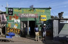 Residents stand outside a spaza convienience shop in Cape Town's Imizamo Yethu township, April 19, 2014. REUTERS/Mike Hutchings