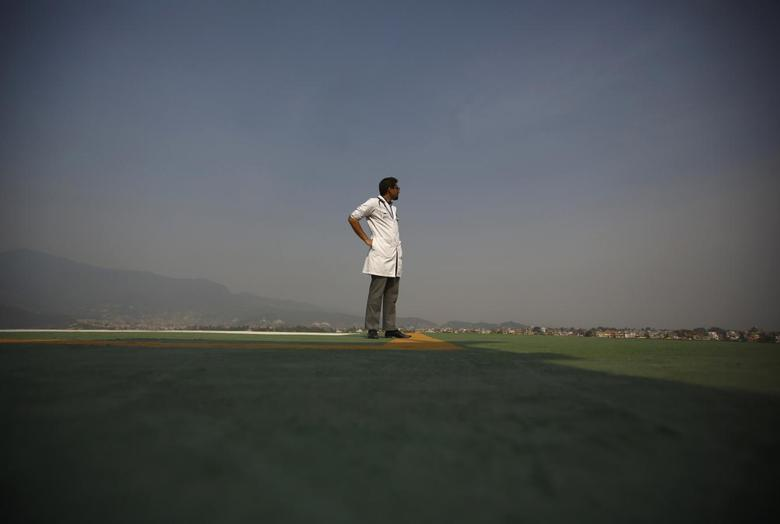 A doctor expecting the arrival of the victims of a Mount Everest avalanche standbys near the helipad at Grandi International Hospital in Kathmandu April 18, 2014. REUTERS/Navesh Chitrakar