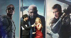 """Actress Scarlett Johansson (R) gestures to the crowd during an interview at the UK premiere of """"Captain America: The Winter Soldier: at Shepherds Bush in London, March 20, 2014. REUTERS/Paul Hackett"""