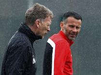 Manchester United's manager David Moyes (L) walks past Ryan Giggs during a training session at the club's Carrington training complex in Manchester, northern England March 18, 2014. REUTERS/Phil Noble/Files