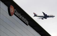 A British Airways airplane flies past a signage for pharmaceutical giant GlaxoSmithKlein (GSK) in London April 22, 2014. REUTERS/Luke MacGregor