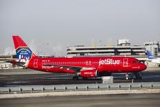 A JetBlue Airbus A320-200 plane with a New York Fire Department logo painted on its side stands on the tarmac of the John F. Kennedy International Airport in New York December 11, 2013. REUTERS/Lucas Jackson