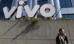 Un hombre conversa por teléfono móvil a las afueras de la sede de la firma de telefonía Vivo en Sao Paulo, Brasil, jun 30 2010. El legendario estadio de Maracaná en Río de Janeiro estaba extasiado. Brasil había aplastado al campeón mundial España. Sin embargo, los 73.000 hinchas de fútbol apenas podían mandar un mensaje de texto para festejar. REUTERS/Nacho Doce