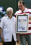 Cuban veteran baseball player Conrado Marrero (L) stands next to Humberto Rodriguez, president of the Cuban Sports Federation, after receiving the Hero of the Cuban Republic medal during the opening ceremony of the XXXV Baseball World Cup in Havana, in this October 12, 2003 file picture. REUTERS/Claudia Daut/Files