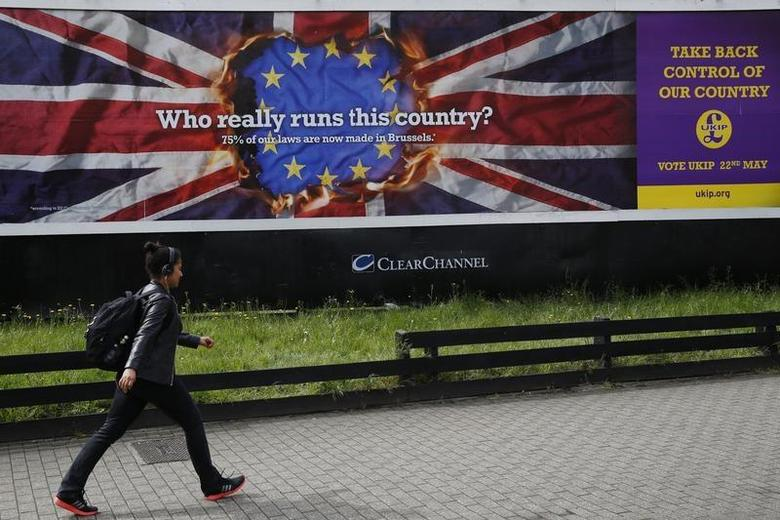 A pedestrian passes a United Kingdom Independence Party (UKIP) European elections campaign poster in Vauxhall, central London April 22, 2014. REUTERS/Luke MacGregor