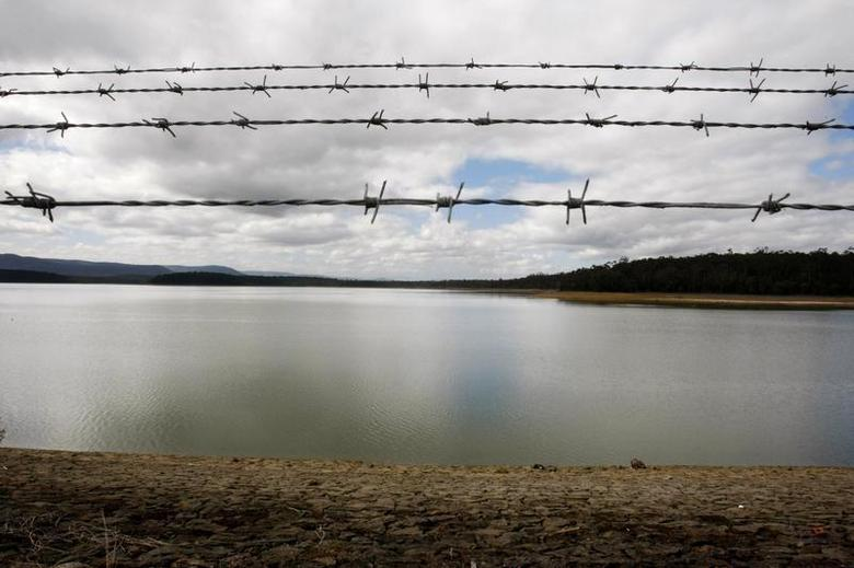 Rows of barbed wire of a fence are seen above the water of the Yan Yean Reservoir north of Melbourne August 28, 2008. REUTERS/Mick Tsikas