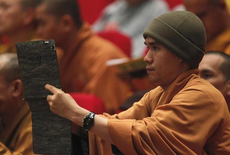 A Buddhist monk films, with an iPad, the closing ceremony of the seventh congress of Vietnam's Buddhist Sangha Association in Hanoi November 24, 2012. REUTERS/Kham