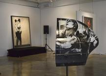 """Paintings titled """"Crazy Horse Car Door"""" and in the background, """"Kissing Coppers"""", by the British street artist Banksy, are seen on display at LMNT Gallery in Miami, Florida February 18, 2014. REUTERS/Zachary Fagenson"""