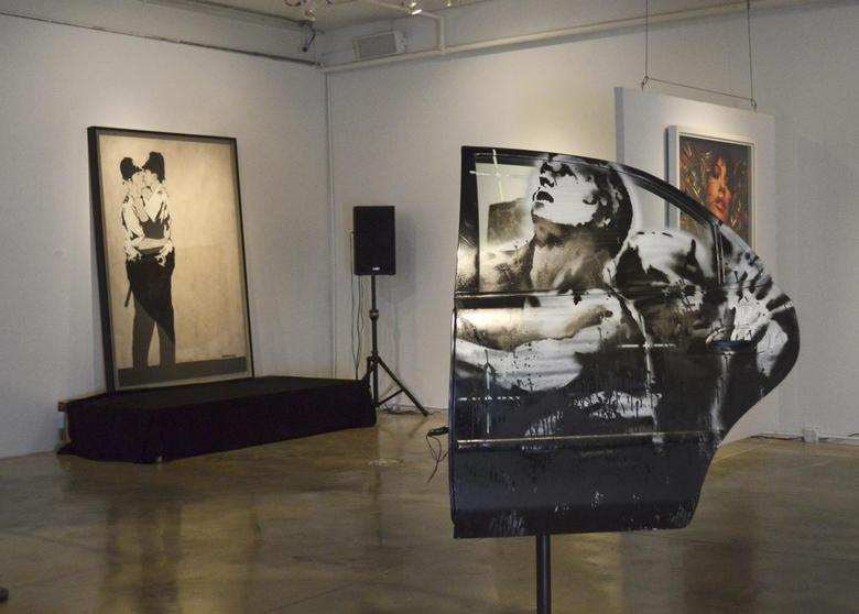 Paintings titled ''Crazy Horse Car Door'' and in the background, ''Kissing Coppers'', by the British street artist Banksy, are seen on display at LMNT Gallery in Miami, Florida February 18, 2014. REUTERS/Zachary Fagenson