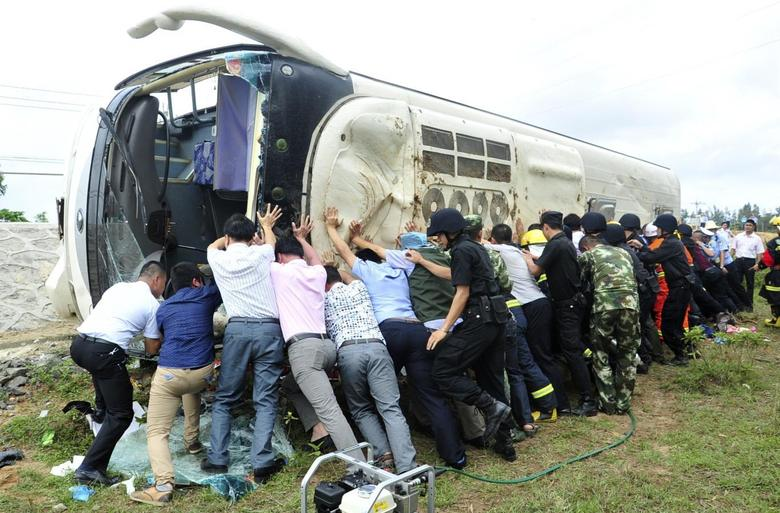 Rescuers attempt to push a bus upright, after it overturned while carrying students from a local primary school, next to a street in Wenchang, Hainan province April 10, 2014. REUTERS/China Daily