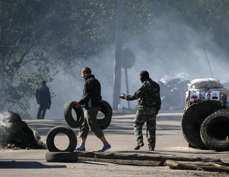 Pro-Russian men stand guard at a checkpoint which was left by Ukrainian security force officers near Slaviansk April 24, 2014. REUTERS/Gleb Garanich