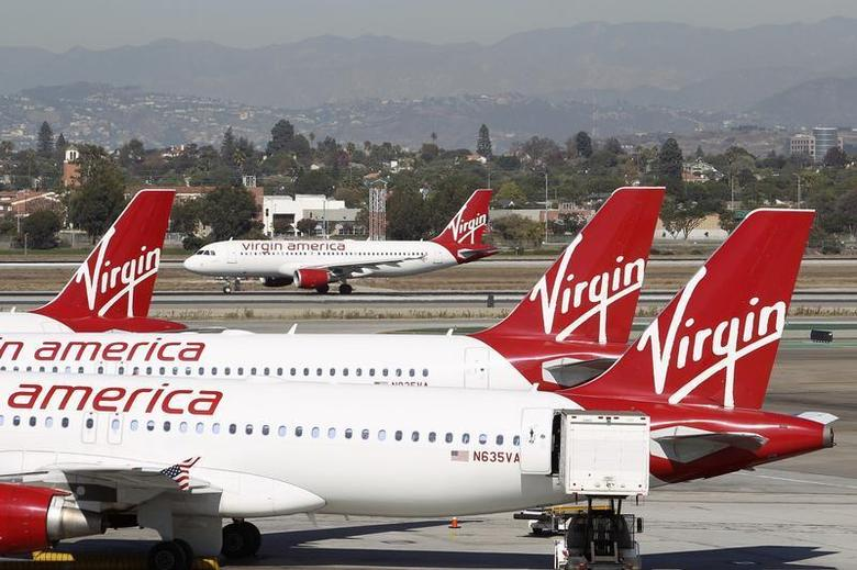 A Virgin America jet takes off past other aircraft parked at Terminal 3 at Los Angeles airport (LAX), California November 2, 2013. REUTERS/David McNew