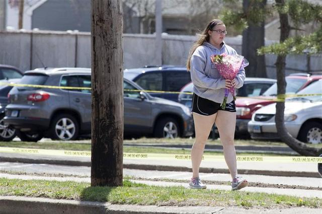 A girl walks with flowers in front of Jonathan Law High School in Milford, Connecticut April 25, 2014. REUTERS/Michelle McLoughlin
