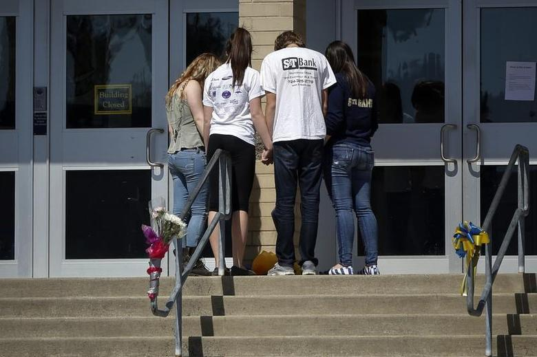 Students hold hands outside the entrance to Franklin Regional High School in Murrysville, Pennsylvania April 10, 2014. REUTERS/Shannon Stapleton