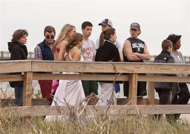 Students arrive at the beach in their prom outfits for a vigil in honor of slain student Maren Sanchez in Milford, Connecticut April 25, 2014. REUTERS/Michelle McLoughlin