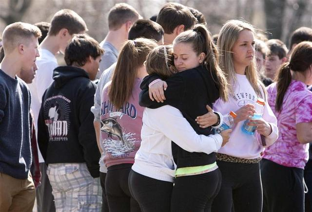 Students mourn in front of Jonathan Law High School in Milford, Connecticut April 25, 2014. REUTERS/Michelle McLoughlin