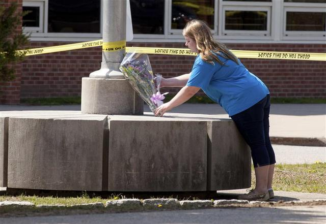 A girl places flowers in front of Jonathan Law High School in Milford, Connecticut April 25, 2014. REUTERS/Michelle McLoughlin