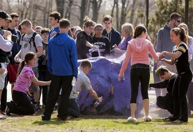 Students gather to spray paint a rock in front of Jonathan Law High School in honor of Maren Sanchez who was killed at the school in Milford, Connecticut April 25, 2014. REUTERS/Michelle McLoughlin