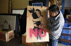 Warehouse manager Ricky Limon picks up a sign made by Banksy at Julien's Auctions in Los Angeles, California April 25, 2014. REUTERS/Lucy Nicholson