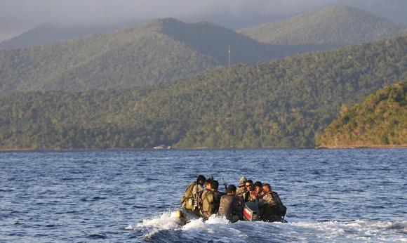 Members of the Philippine marines are transported on a rubber boat from a patrol ship after conducting a mission on the disputed Second Thomas Shoal, part of the Spratly Islands in the South China Sea, as they make their way to a naval forces camp in Palawan province, southwest Philippines March 31, 2014. REUTERS/Erik De Castro