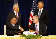 U.S. President Barack Obama (standing R) and Malaysian Prime Minister Najib Razak (standing L) witness the signing of a major business agreement between GE and AirAsia X in Kuala Lumpur, Malaysia, April 28, 2014. Seated at left is CEO of AirAsia Tony Fernandez, and for CEO GE John Rice. REUTERS/Larry Downing