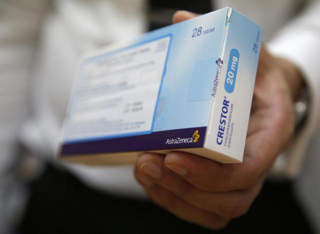 A box of the drug ''Crestor'' made by pharmaceutical manufacturer AstraZeneca, is held by a pharmacy worker as he poses for a photograph at a pharmacy in London April 28, 2014. REUTERS/Luke MacGregor